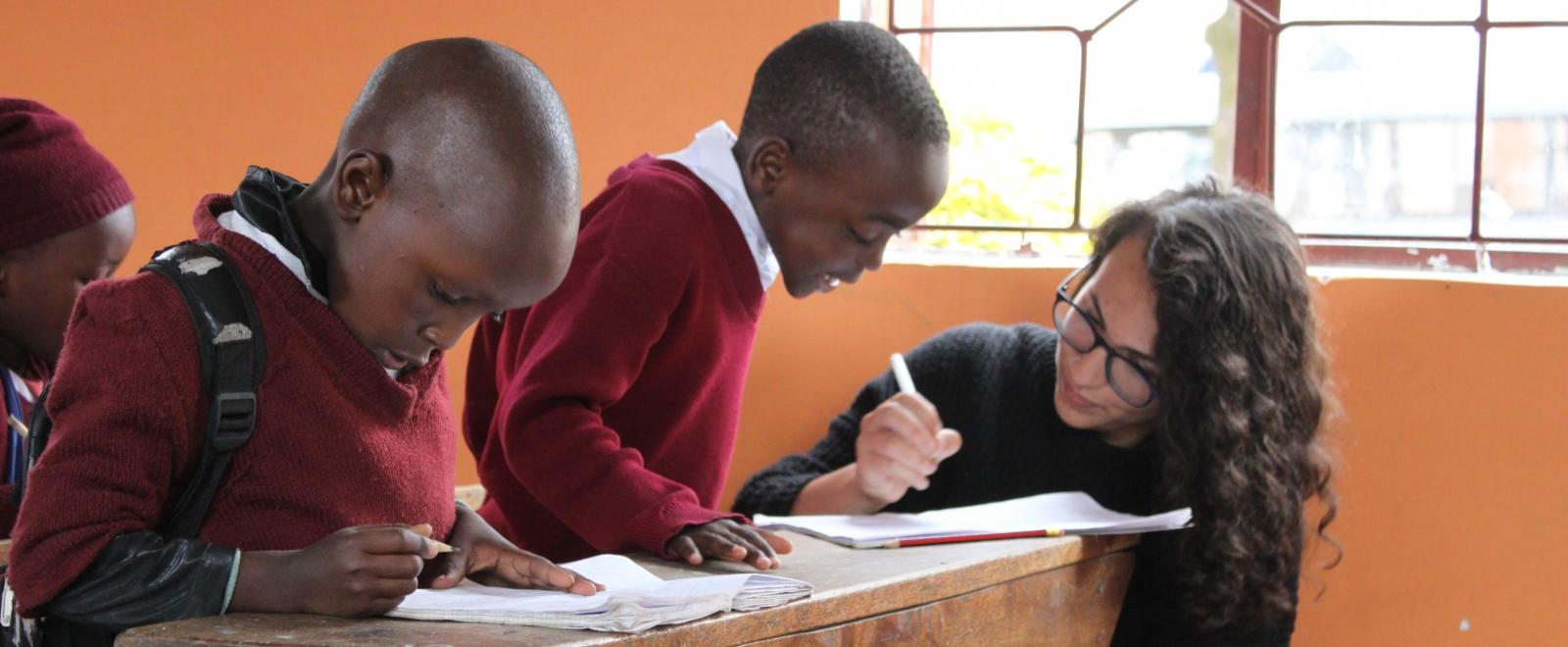 A high school special volunteer helps a child with a task in the classroom